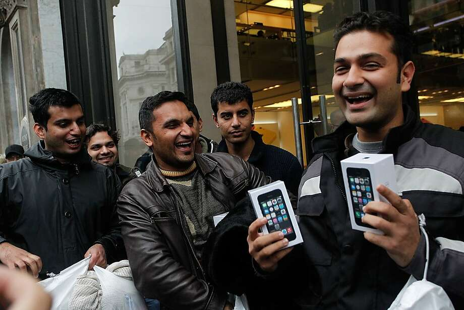 Ecstatic people celebrate with their new iPhones outside the flagship Apple store on Regent Street on Friday in London, England. Some consumers have queued for five days, sleeping in makeshift tents, to be the first to own the new updated iPhone. Photo: Mary Turner, Getty Images