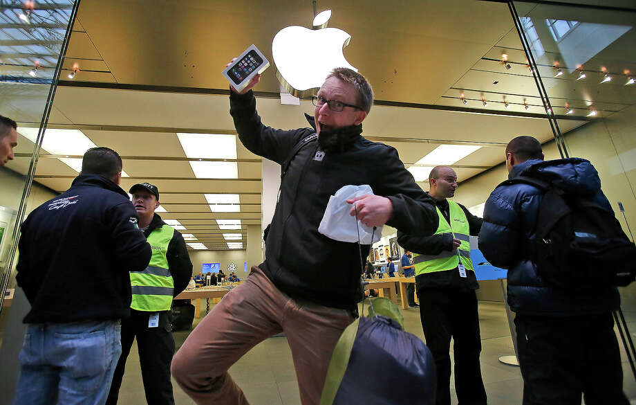 A customer of the Apple store in Oberhausen celebrates with the new iPhone 5S as he leaves the store at the start of the new iPhone sale in Oberhausen, Germany, Friday. Photo: Frank Augstein, ASSOCIATED PRESS / AP2013