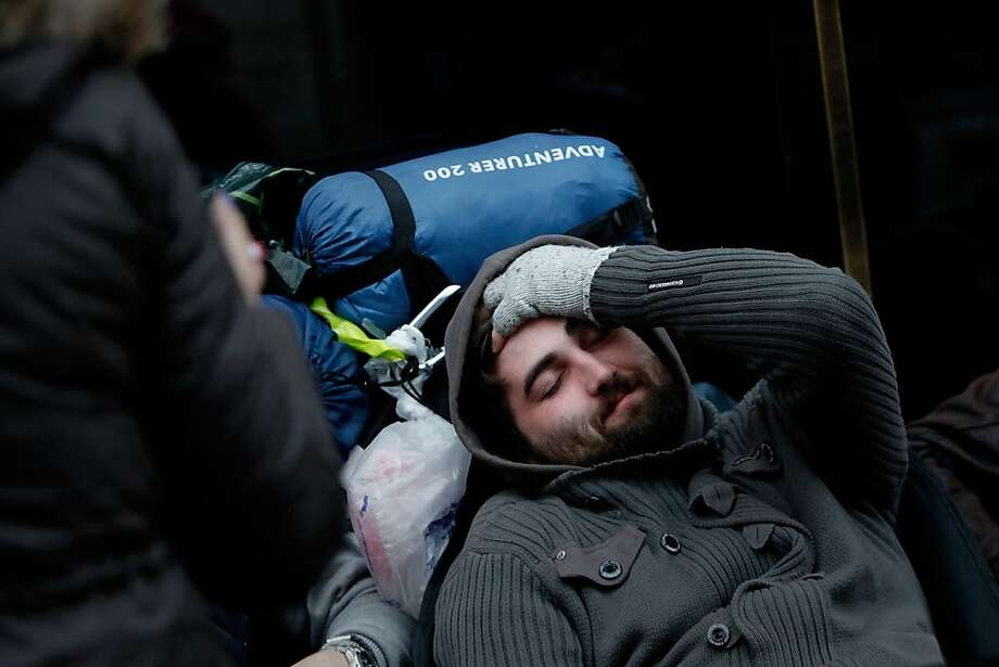 Michael Robinson sits outside the Apple Store where he has queued for five days, at Regent Street on Friday in London, England. Some consumers have queued for five days, sleeping in makeshift tents, to be the first to own the new updated iPhone. Photo: Mary Turner, Getty Images