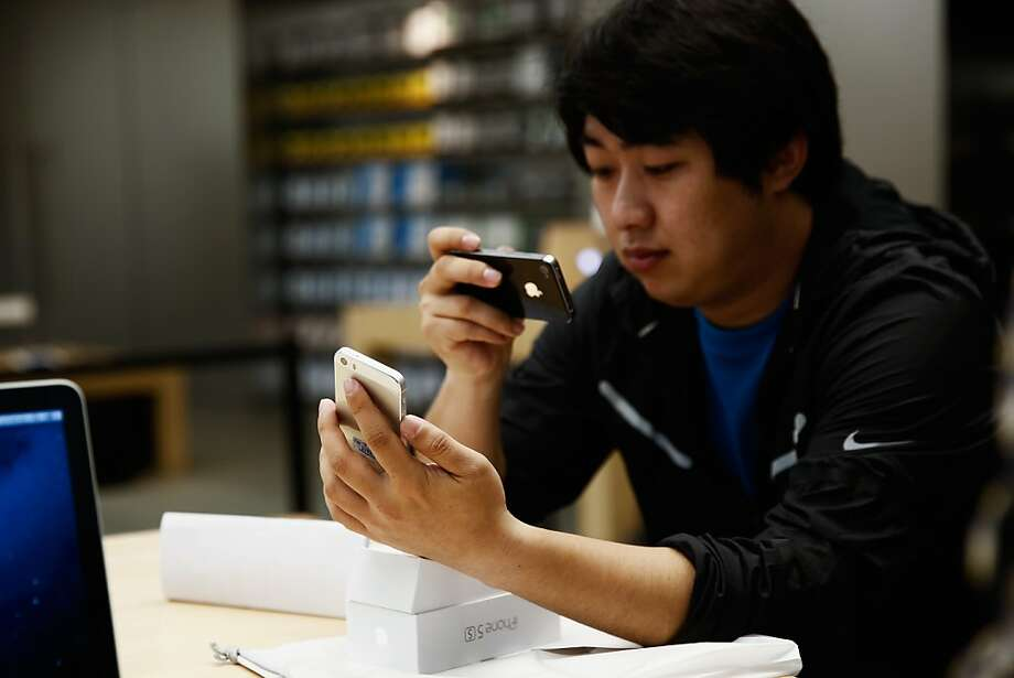 A customer inspects the new iPhone 5s at the Wangfujing flagship store on Friday in Beijing, China. Apple launched the new iPhone 5C model that will run iOS 7 is made from hard-coated polycarbonate and comes in various colors and the iPhone 5S that features fingerprint recognition security. Photo: Lintao Zhang, Getty Images