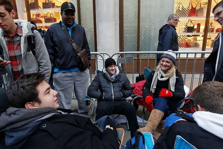 Charlotte and Oli Mcilroy from Kent, queue outside the Apple store at Regent Street on Friday in London, England. Some consumers have queued for five days, sleeping in makeshift tents, to be the first to own the new updated iPhone. Photo: Mary Turner, Getty Images