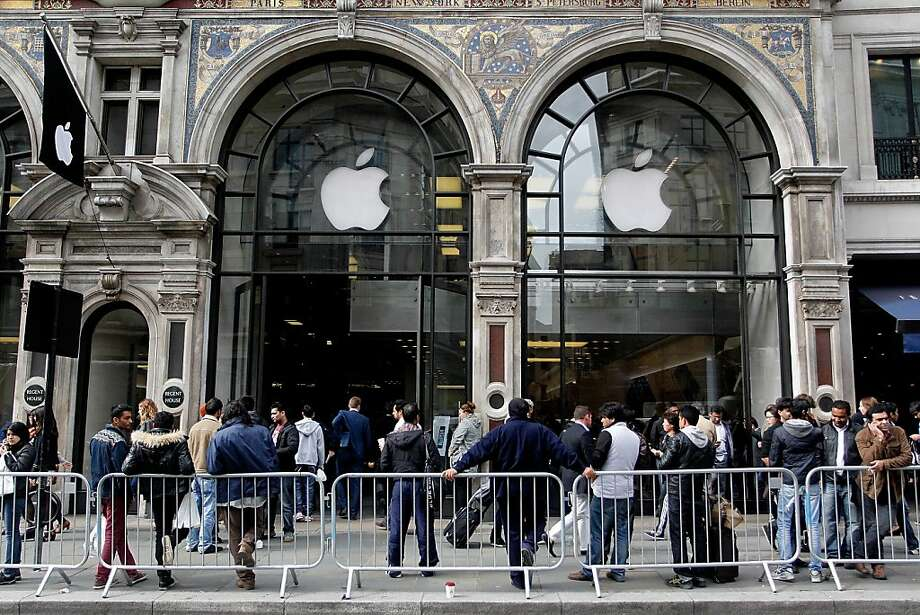 Customers keen to buy the new iPhone 5S, fill the pavement outside the busy Apple store on Regent Street on Friday in London, England. Some consumers have queued for five days, sleeping in makeshift tents, to be the first to own the new updated iPhone. Photo: Mary Turner, Getty Images
