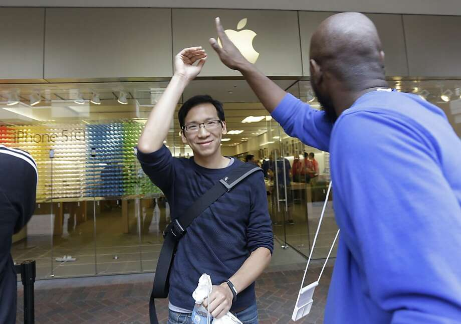 Simon Sun, left, gets a high five from Apple sales associate Mike Jones, right, during the opening day of new iPhone 5S and iPhone 5C sales in Richmond, Va., Friday. Photo: Steve Helber, Associated Press