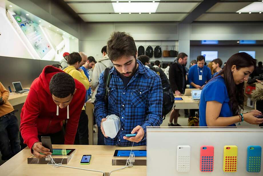 Gregory Rocco, of Brooklyn, New York, looks at an iPhone 5C on display at the Fifth Avenue Apple store on Friday in New York City. Apple launched two new models of iPhone: the iPhone 5S, which is preceded by the iPhone 5, and a cheaper, paired down version, the iPhone 5C. The phones come with a new operating system. Photo: Andrew Burton, Getty Images
