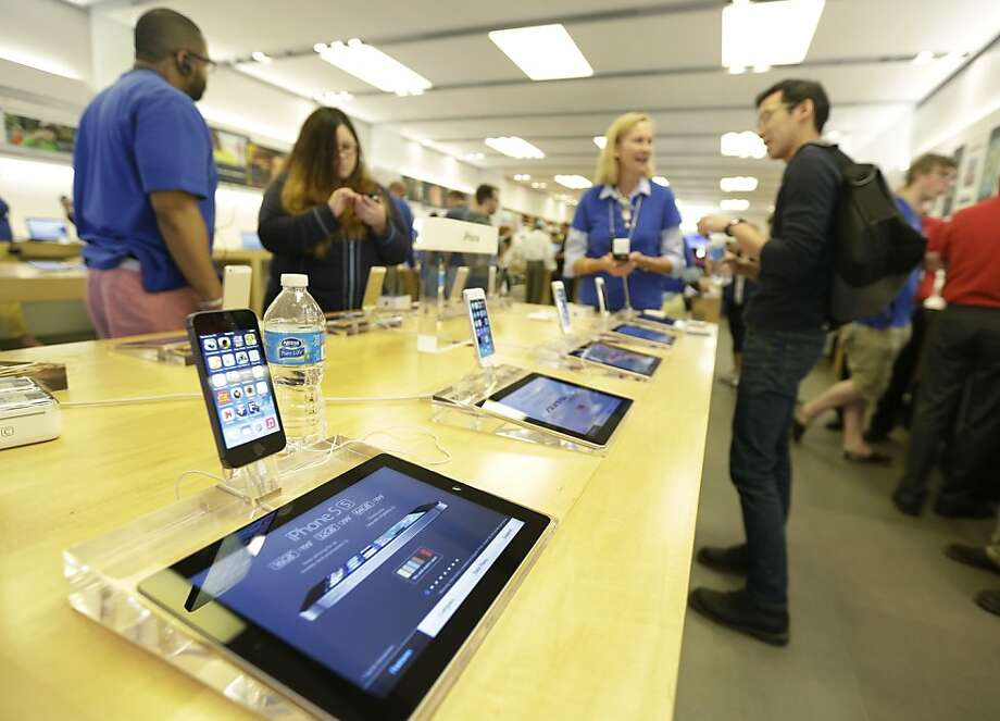 New iPhone 5S are on display at an Apple store in Richmond, Va., Friday. Apple is releasing two different iPhone models at once. The pricier one, at $199 with a two-year contract, sports a fingerprint sensor, a better camera and a faster processor. The fingerprint sensor alone is worth the $100 more you'll pay over an iPhone 5C. Photo: Steve Helber, Associated Press
