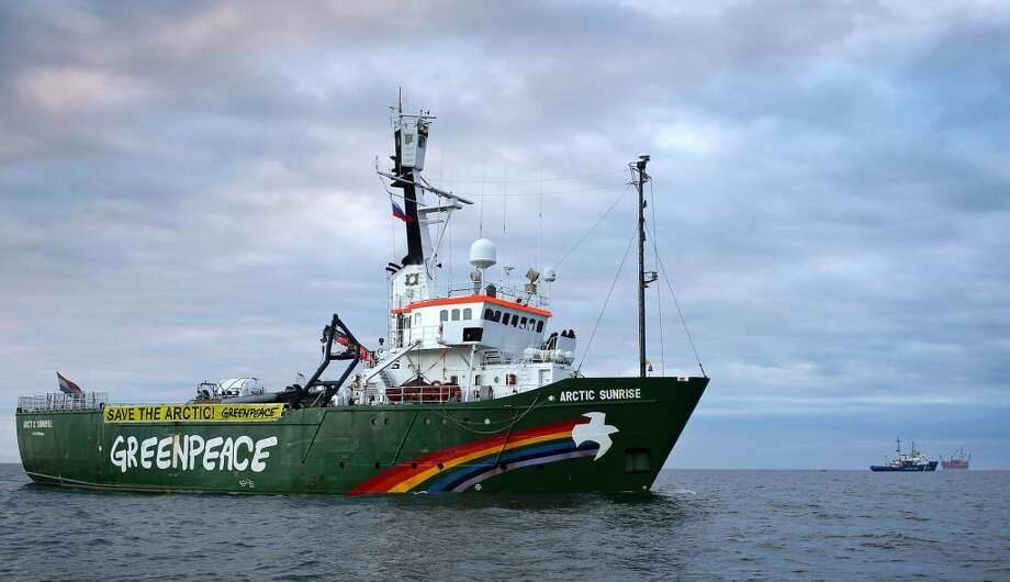 The Arctic Sunrise, Greenpeace's Arctic protest ship, travels off Russia's north-eastern coast in the Pechora Sea with a Russian Coast Guard ship (back 2nd right) and Gazproms Prirazlomnaya Arctic oil platform (back right) drifting in the background. Photo: DENIS SINYAKOV, AFP/Getty Images