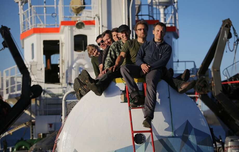 Greenpeace activists pose atop a 'safety pod' on board of the Arctic Sunrise. The Russian Coast Guard is towing the Greenpeace ship, Arctic Sunrise, toward the nearest port after armed officers stormed it following a protest against oil drilling in Arctic waters. Photo: Denis  Sinyakov, Associated Press
