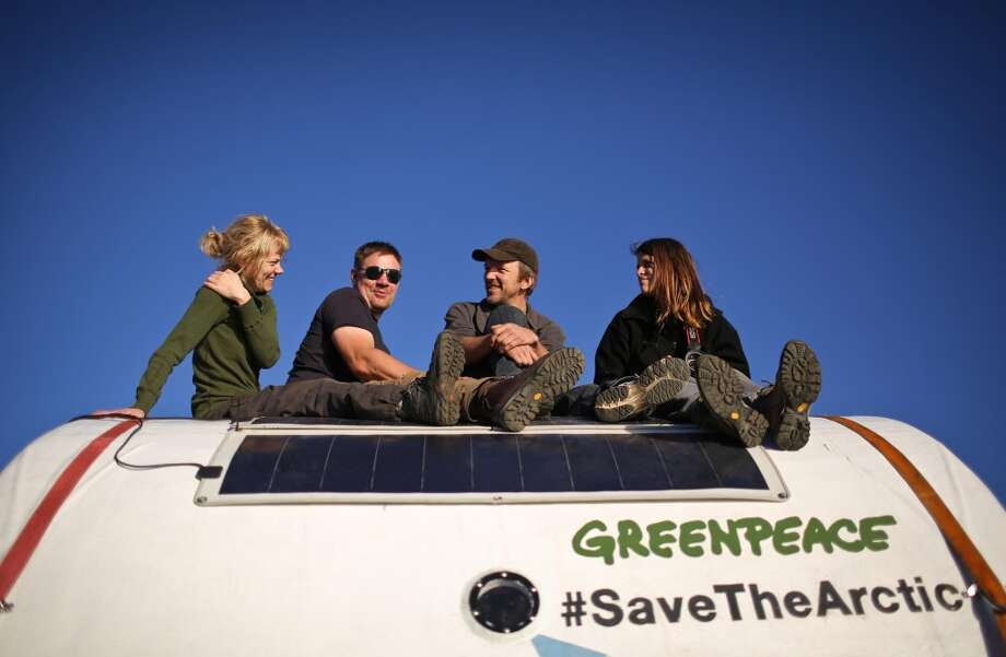 Greenpeace climbers  Sini Saarela from Finland,  Anthony Perrett and Phillip Ball from Britain and Camila Speziale from Argentina sit atop a 'safety pod' on board the Arctic Sunrise. The Russian Coast Guard towed the Greenpeace ship, Arctic Sunrise, toward the nearest port after armed officers stormed it following a protest against oil drilling in Arctic waters. Photo: Denis  Sinyakov, Associated Press