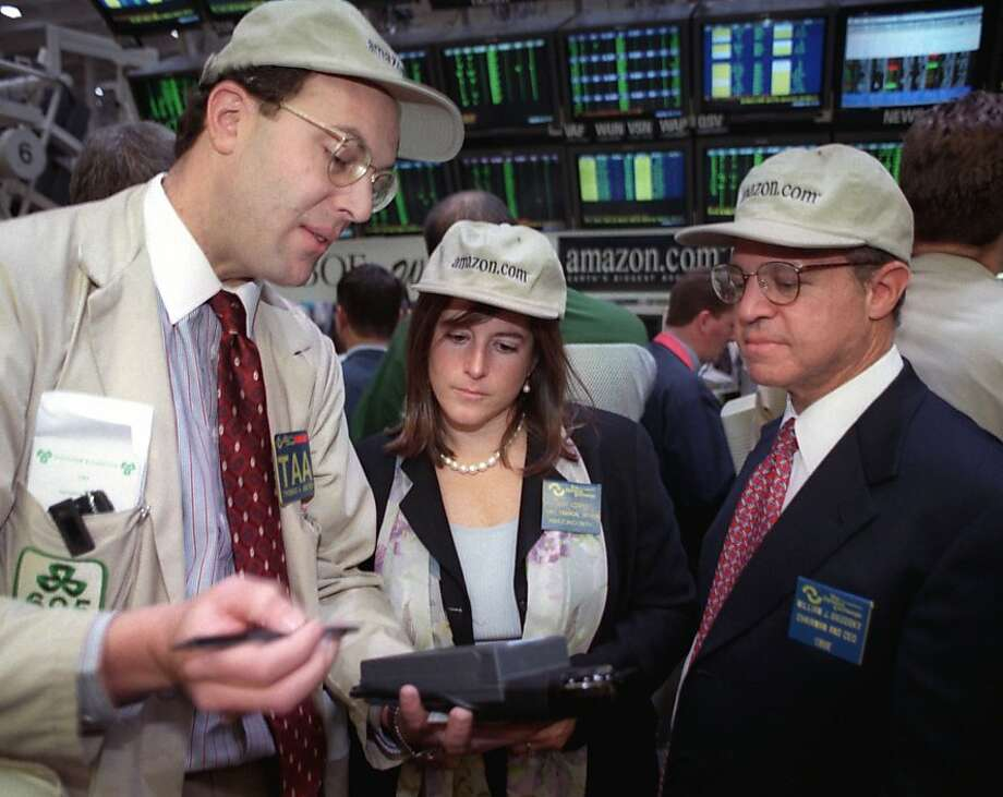 Joy Covey, chief financial officer of Seattle-based Amazon.com, Inc., gets pointers on trading using a hand-held market maker terminal at the Chicago Board Options Exchange on Wednesday, Nov. 19, 1997, by Thomas Ascher, left, vice chairman, and William Brodsky, chief executive officer of the exchange. It was the first day of trading options Wednesday for Amazon. Photo: Chicago Board Options Exchange, AP