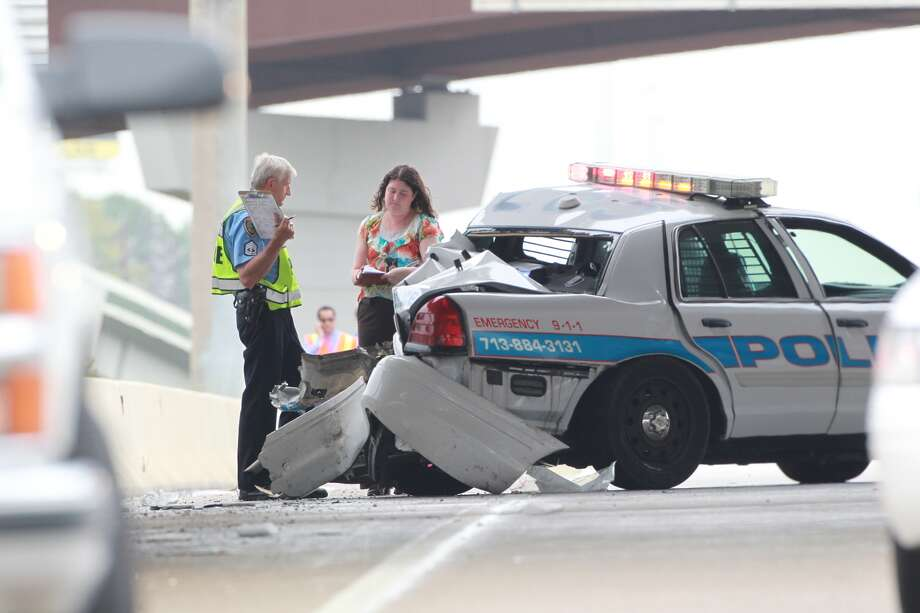 Houston police help clear a crash which injured a fellow officer on the Eastex Freeway near Sam Houston Parkway Friday afternoon. (Mayra Beltran/Houston Chronicle) Photo: Mayra Beltran, Houston Chronicle