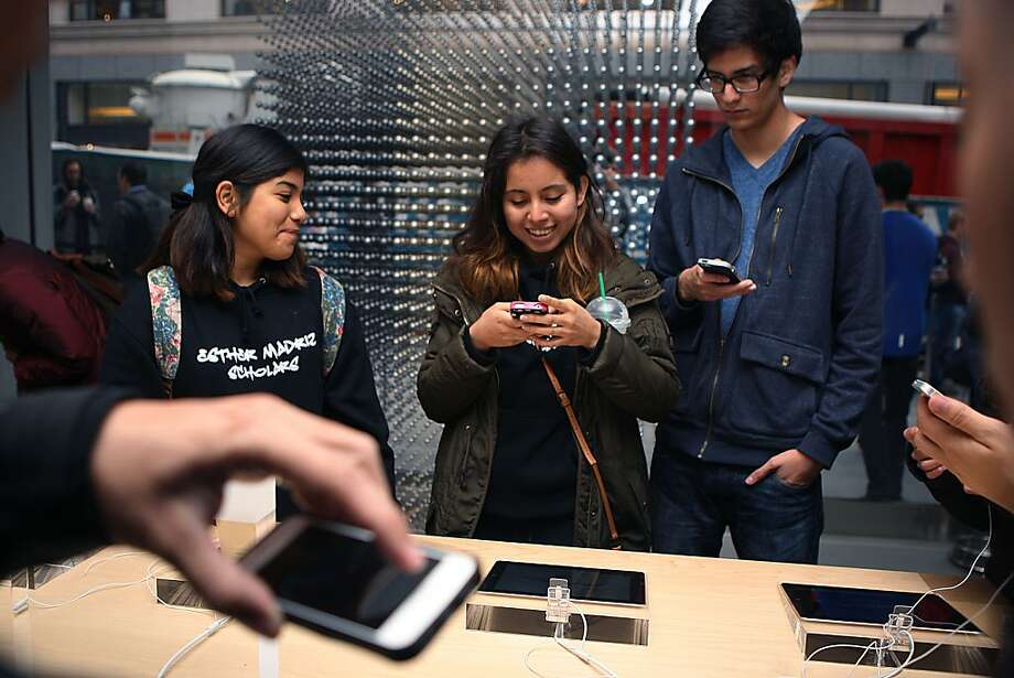 Natalie Moreira (left), Evelyn Zamora and Brandon Fuentes check out the new iPhones after waiting in line since 4 a.m. Photo: Liz Hafalia, The Chronicle