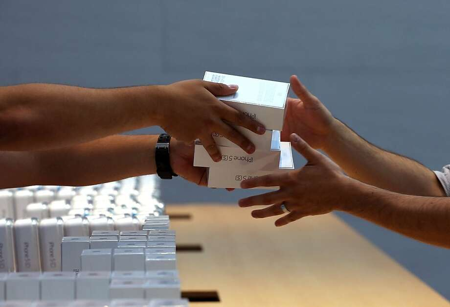 Must. Have. Newest. Thing.:Apple Store employees pass boxes of the new Apple iPhone 5S in Palo Alto, Calif.  Photo: Justin Sullivan, Getty Images