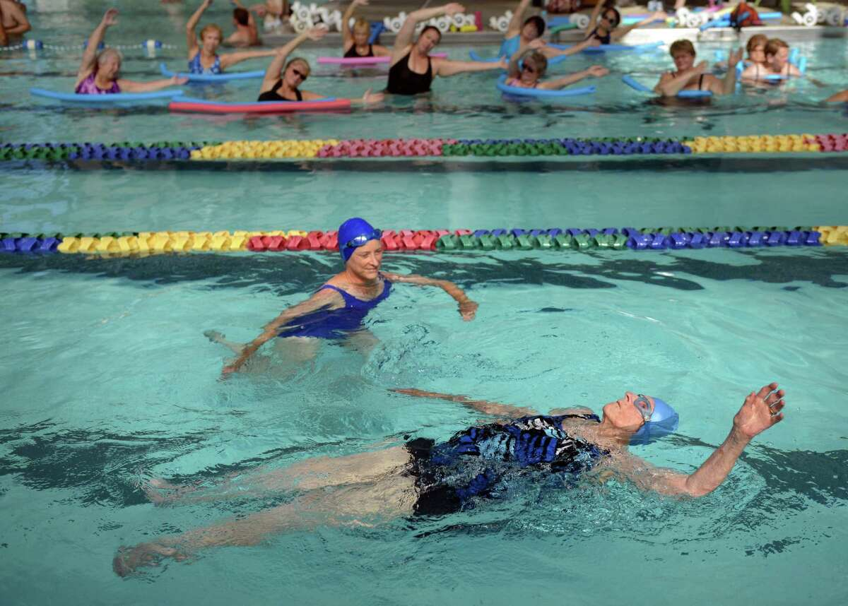 Margaret Wachs celebrates her 100th birthday with a 1/4 mile swim as a fundraiser for the Stratford United Methodist Church Friday, Sept. 20, 2013 at the Woodruff Family YMCA in Milford, Conn. One of her five daughters Elaine Matto, of Shelton, joins her in the pool.