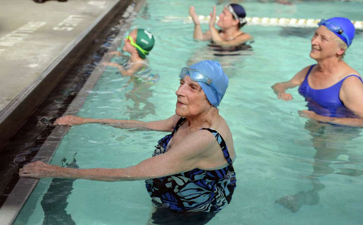 Margaret Wachs celebrates her 100th birthday with a 1/4 mile swim as a fundraiser for the Stratford United Methodist Church Friday, Sept. 20, 2013 at the Woodruff Family YMCA in Milford, Conn. Wachs finished the 10 laps to a round of applause from family, friends, and YMCA members who stopped to watch her swim. Wachs was joined in the pool by her daughter, Elaine Matto, of Shelton, far right, her granddaughter Amy Weintraub, of Brooklyn, NY, and her 6-year-old great-granddaughter Natalie Johanesen.