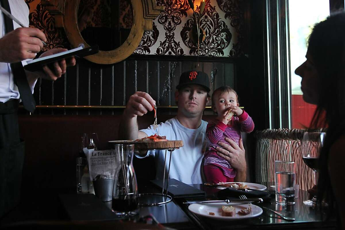 Michael Blake, center, holds his daughter Anna, 10 months, as he gets a taste of an appetizer while his wife Corey, right, orders her meal September 19, 2013 at the new Cafe Claude location in the Marina in San Francisco, Calif.