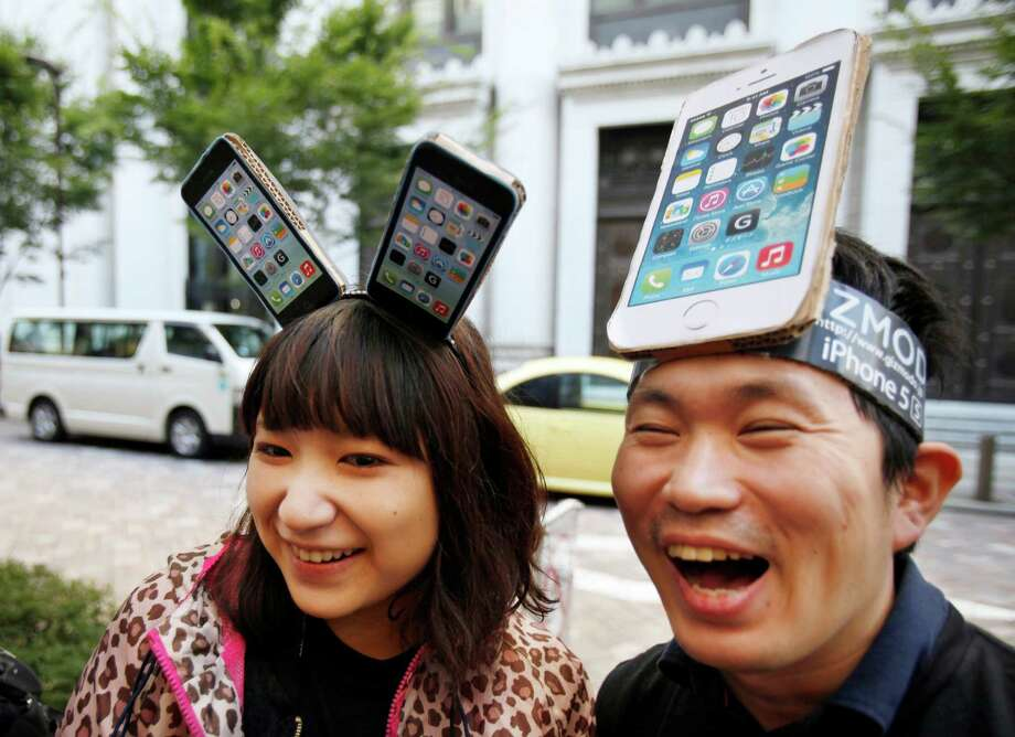 Tech heads: Yui Kashima, left, and Nobuhiko Matsuda wait to purchase an Apple's new iPhone outside a store in Tokyo. Photo: Associated Press