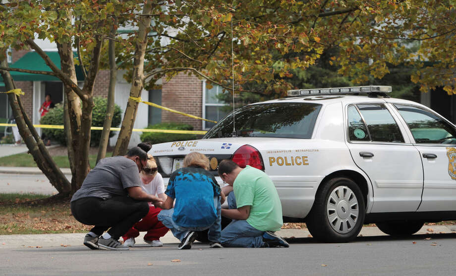 Praying for the fallen: People bow down behind an Indianapolis Metropolitan Police Department squad car to pray for slain IMPD Officer Rod Bradway, 41, and his family. Photo: Associated Press