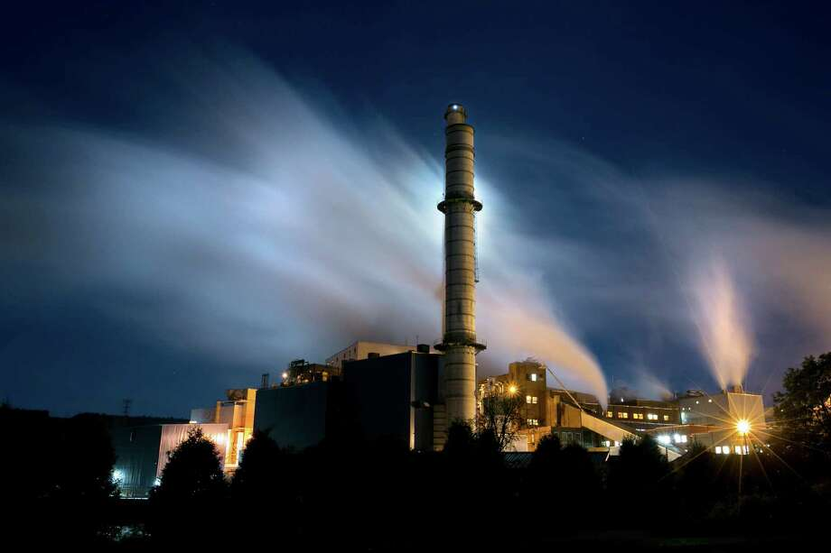 A different kind of moonscape:Steam from the Verso paper mill is backlit by the light of the setting moon in this time-exposure. Photo: Associated Press