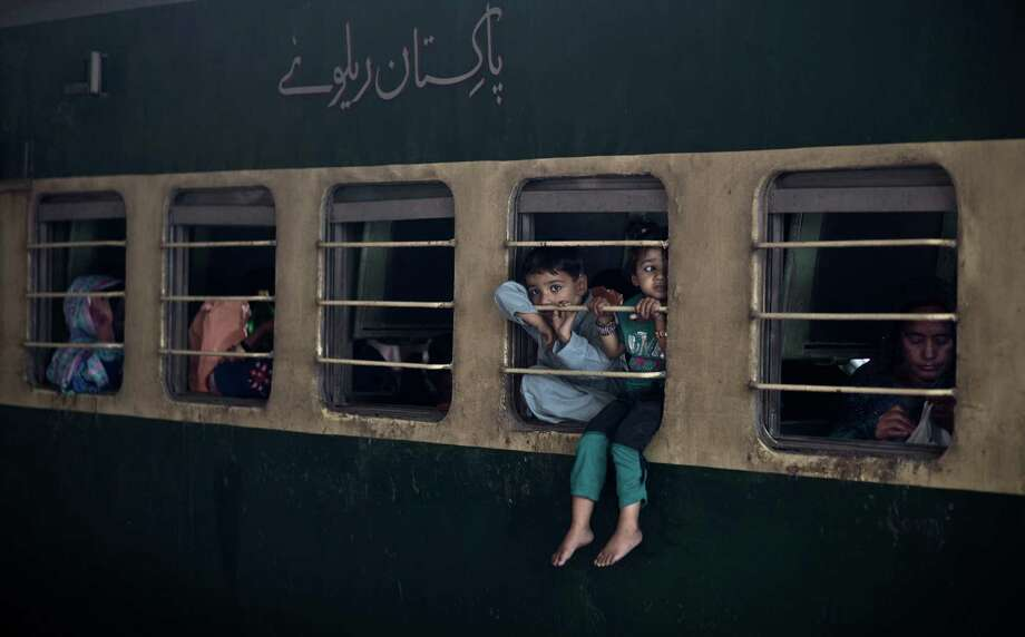 Hanging out: While waiting to travel with their family from Rawalpindi to Peshawar, Pakistani children sit on the window of a train, to escape the heat trapped inside the cabin, as temperatures reached 91.4 degrees Fahrenheit, at Rawalpindi railway station. Photo: Associated Press