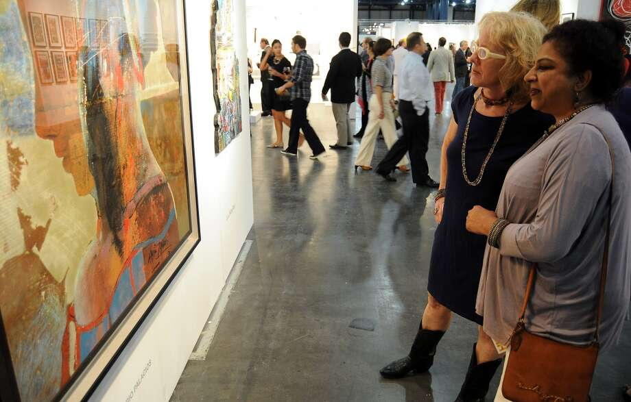 Sarah Gish and Kalyani Giri look at a painting at the opening night of the Houston Fine Arts Fair at the George R. Brown Convention Center Thursday Sept.19 2013.(Dave Rossman photo) Photo: For The Houston Chronicle