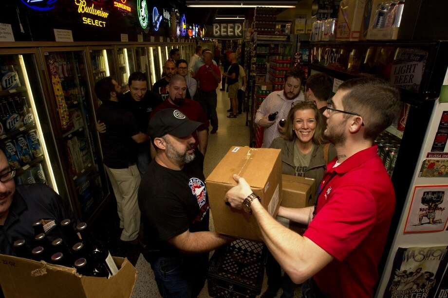 Jordan Duncan, left, and Carol Self, center, receive a case of beer from Spec's beer department manager Joey Williams, right, at the release of the new beer Friday, Sept. 20, 2013, in Houston. The beer, Sick in the Head, is a tribute to Williams who successfully battled brain cancer. Each bottle sells for $10, and a portion of sales will go to cancer research. (Cody Duty / Houston Chronicle) Photo: Houston Chronicle