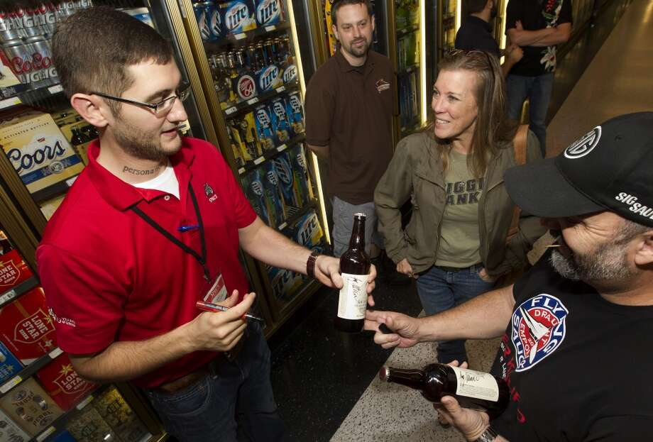 Spec's beer department manager Joey Williams, left, hands a signed beer to Carol Self, center, and Jordan Duncan right, at the release of the new beer Friday, Sept. 20, 2013, in Houston. The beer, Sick in the Head, is a tribute to Williams who successfully battled brain cancer. Each bottle sells for $10, and a portion of sales will go to cancer research. (Cody Duty / Houston Chronicle) Photo: Houston Chronicle