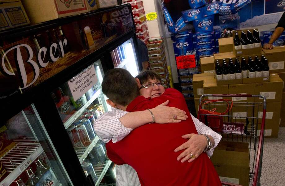 Spec's beer department manager Joey Williams, left, hugs his mom, Nora Williams, right, at the release of a new beer Friday, Sept. 20, 2013, in Houston. The beer, Sick in the Head, is a tribute to Joey, who successfully battled brain cancer. Each bottle sells for $10, and a portion of sales will go to cancer research. (Cody Duty / Houston Chronicle) Photo: Houston Chronicle