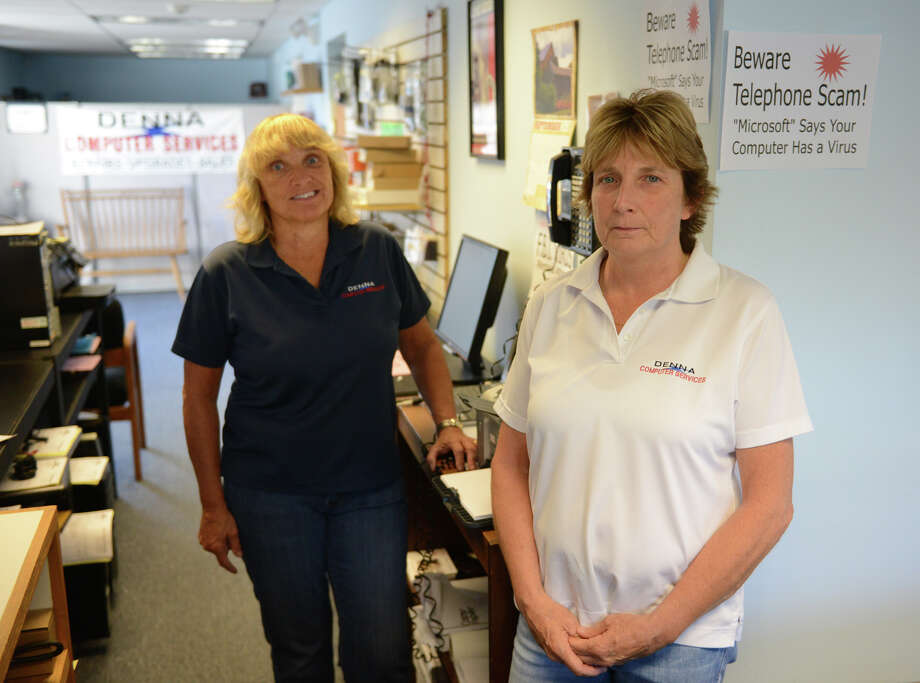 Nancy Lavoie, left, and Debbie Macintyre, co-owners of DENNA Computer Services in Brookfield, Conn., inside their shop on Friday, Sept. 20, 2013.  They have been dealing with many customers who are the victims of phone scams invloving computers and have spoken out on the issue, putting up signs inside their store. Photo: Tyler Sizemore / The News-Times