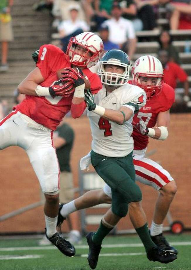 Katy sophomore defensive back Travis Whillock, left, backed up by junior teammate Sy Slater, right, makes an interception on a pass intended for The Woodlands senior wide receiver Tyler Patrick.