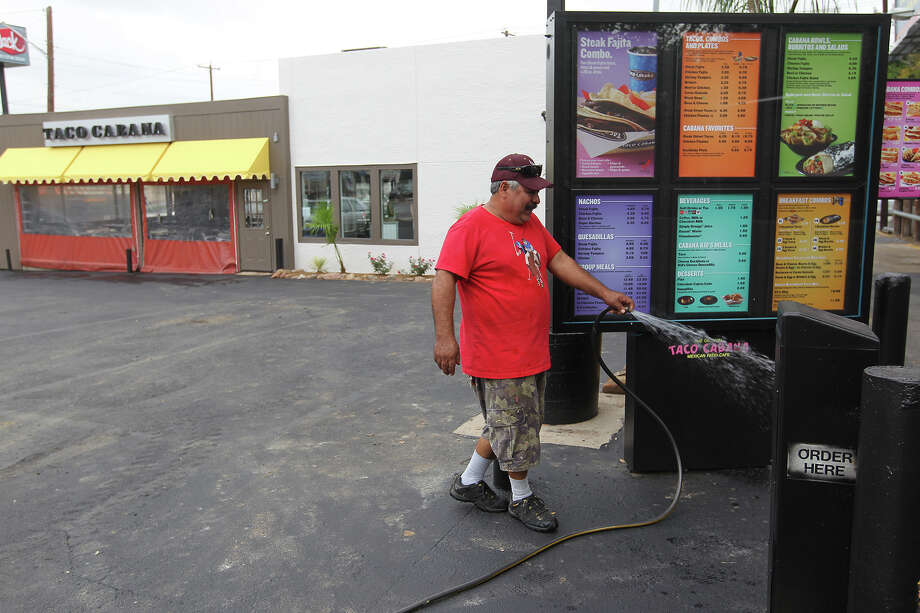 Contract worker Miguel Jimenez washes the parking lot of the company's first Taco Cabana at the corner of San Pedro and Hildebrand, Tuesday, Sept. 17, 2013. The company is celebrating its 35th anniversary and will host a grand re-opening of the location on Sept. 21. Photo: JERRY LARA, San Antonio Express-News / © 2013 San Antonio Express-News