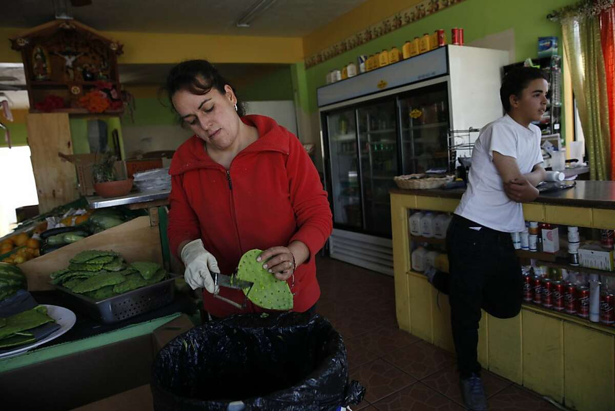 Emelia Gonzalez (l to r) removes Nopales spines from the pads at her store, Lupita's Produce, as her son Richard Luna, 14, stands at the counter on Wednesday, July 17, 2013 in Salinas, Calif.