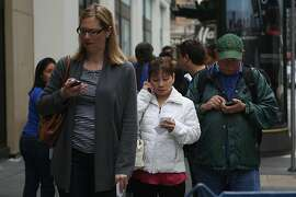 Julie Swift (on phone in foreground) waits in line to get her  new iPhone at the Apple store on Stockton St. in San Francisco, California, on Friday, September 20, 2013.