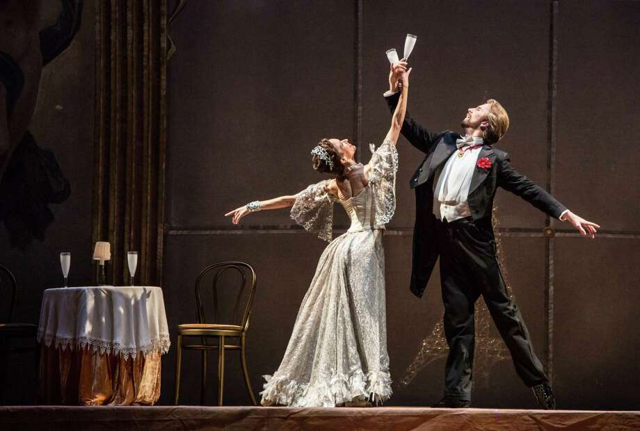 "Mireille Hassenboehler and Linnar Looris raise a glass to happiness - and life - in Ronald Hynd's ""The Merry Widow."" Houston Ballet's production continues through Sept. 29, when Hassenboehler retires after 20 years with the company. Photo: Amitava Sarkar"