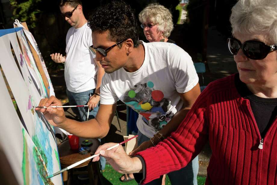From right to left, Beth Grieser, Gabriel Diaz, Nancy McBride and Sage Mitchell paint a Seattle skyline in watercolor as part of a station sponsored by Mind Unwind Gallery during the annual PARK(ing) Day on California Ave Southwest and Southwest Walker Street in West Seattle. Photo: JORDAN STEAD, SEATTLEPI.COM / SEATTLEPI.COM
