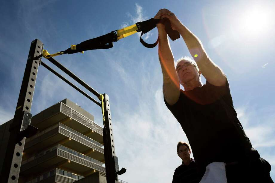 Portrait photographer Michael Rosenberg, right, of Vashon Island, is led in a workout by Dominick Viscardi, background, as part of a station sponsored by Equilibrium Fitness during the annual PARK(ing) on 44th Avenue Southwest and Southwest Edmunds Street in West Seattle. Photo: JORDAN STEAD, SEATTLEPI.COM / SEATTLEPI.COM