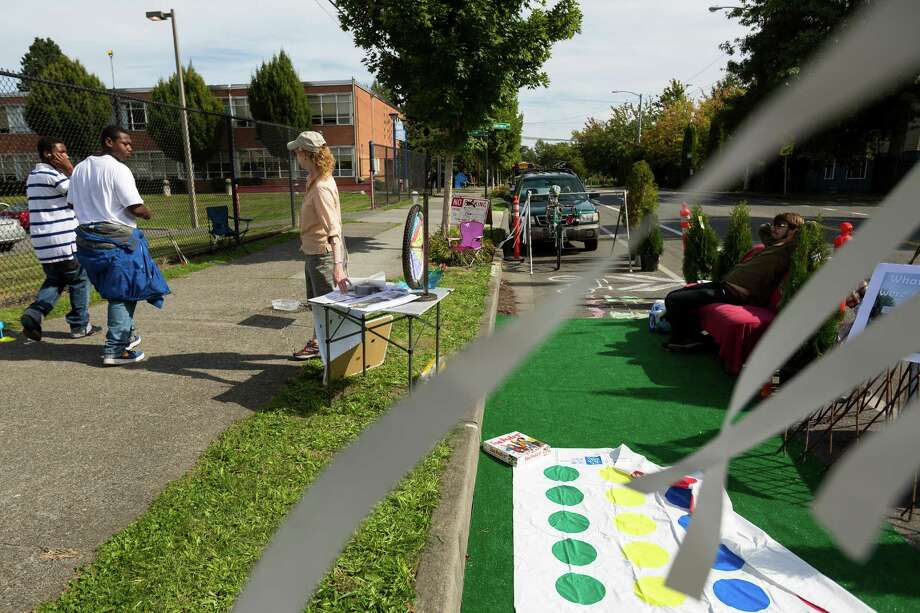 Sue Abbott, center left, and Noah Pylvainen, right, run a station sponsored by Rainier Valley Greenways as part of the annual PARK(ing) Day outside of Rainier Beach High School in Seattle. Photo: JORDAN STEAD, SEATTLEPI.COM / SEATTLEPI.COM