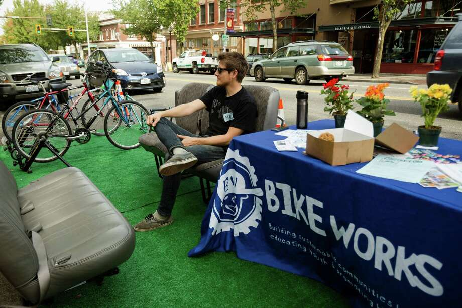 Neil Larsen, of BikeWorks, waits for people to cycle in place as part of the annual PARK(ing) Day at their space on Rainier Avenue South and South Ferdinand Street in Seattle. PARK(ing) Day is an open-source global event where collaborators temporarily transform metered parking spaces into sites for temporary public activities. Photo: JORDAN STEAD, SEATTLEPI.COM / SEATTLEPI.COM