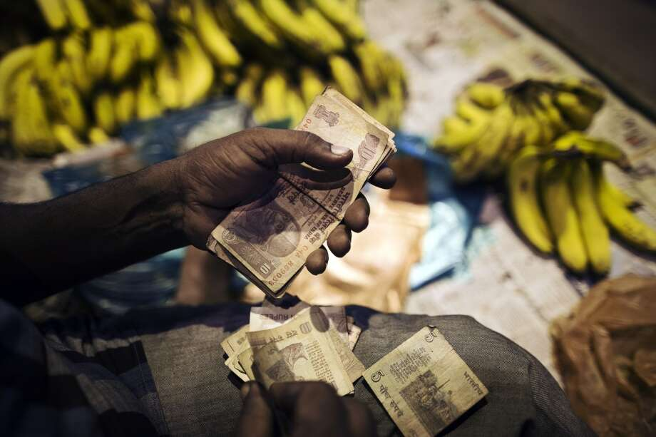 India: A fruit vendor counts rupee banknotes of various denominations at his stall in the old Delhi area of New Delhi, India. The Federal Reserve's decision to postpone its rollback of U.S. stimulus offered Asian policy makers extra time to address domestic economic fragilities as the region copes with diminished capital inflows. Photo: Prashanth Vishwanathan, Bloomberg