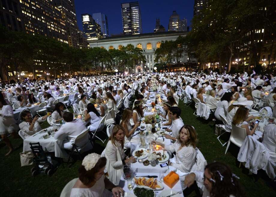 New York City: Guests are seated for dinner at Bryant Park during the annual  Diner en Blanc, the worlds only viral culinary event, a chic secret pop-up style picnic imported from France. Celebrating its 25th anniversary,  the outdoor site -- always a landmark location -- is revealed at the last-minute. Guests are asked to dress entirely in elegant white, bring a picnic basket of food, fine china and silverware, white tablecloths, table and chairs. Photo: Timothy Clary, AFP/Getty Images