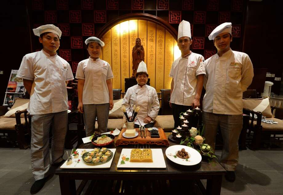 China: Chef Wang Xinglan (C) with other chefs who specialize in Confucius cuisine with some of her dishes at a restaurant in Jinan, Shandong Province.  The fine-dining trend is a reflection of how the ruling Communist party which long saw the sage as a reactionary force, has now drafted him into its modern campaign to boost China's cultural standing and commerce. The philosopher lived from 551 to 479 BC, and his teachings of hierarchy, order and deference had deep resonance in the feudal societies of China and the region Photo: Mark Ralston, AFP/Getty Images