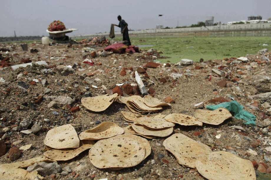 India: Discarded rotis, or Indian bread, along the river bank as an Indian man cleans clothes in the polluted Sabarmati River in Ahmadabad, India. In a United Nations Food and Agricultural Organization report released Wednesday, Sept. 11, 2013 by the Rome-based food agency, one-third of all food produced in the world gets wasted, amounting to an annual loss of $750 billion ($995 billion). The report said food waste hurts the environment by causing unnecessary carbon emissions, extra water consumption and the reduction of biodiversity as farming takes over more land. The most serious areas of waste are of cereals in Asia and meat in wealthy regions and Latin America. Photo: Ajit Solanki, Associated Press