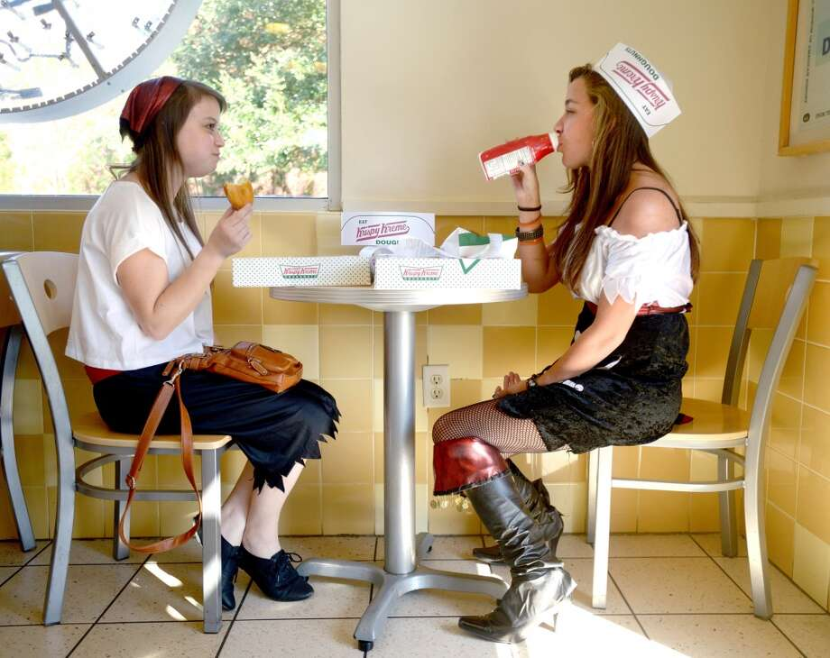 "Florida: Claire Garea, left, and Rhianna Dalton eat doughnuts at Krispy Kreme Doughnuts in Destin, Fla., on ""International Talk Like a Pirate Day,"" Thursday, Sept. 19, 2013. The restaurant gave away a dozen doughnuts to anyone who showed up dressed like a pirate and a single doughnut to anyone who talked like a pirate. Photo: Nick Tomecek, Associated Press"