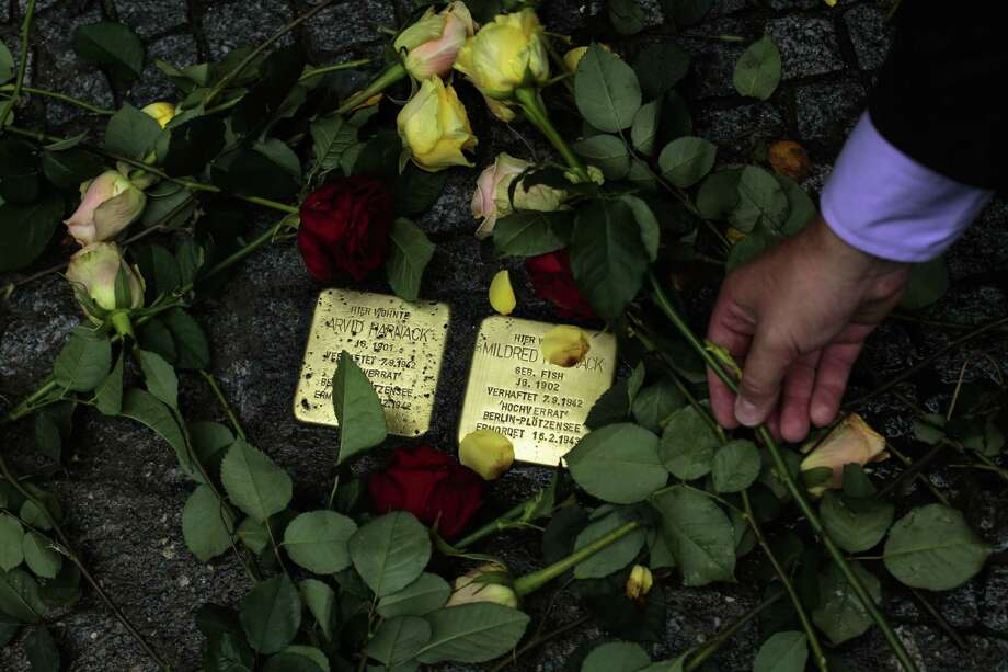 Flowers are placed near the so-called stumbling stones set by a German artist to remember Nazi victim Mildred Fish-Harnack and her husband, Arvid Harnack, in front of the last home they occupied in Berlin. Photo: Markus Schreiber / Associated Press