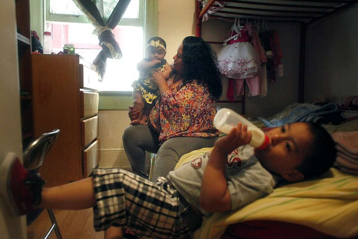 Sonia Cauich (center), holds her daughter Natalia Dorantes (left), 6 months, as she cares for her son, Anthony Hernandez (bottom), 3, and daughter Natalia Dorantes at home on Friday, September 20, 2013 in San Francisco, Calif.