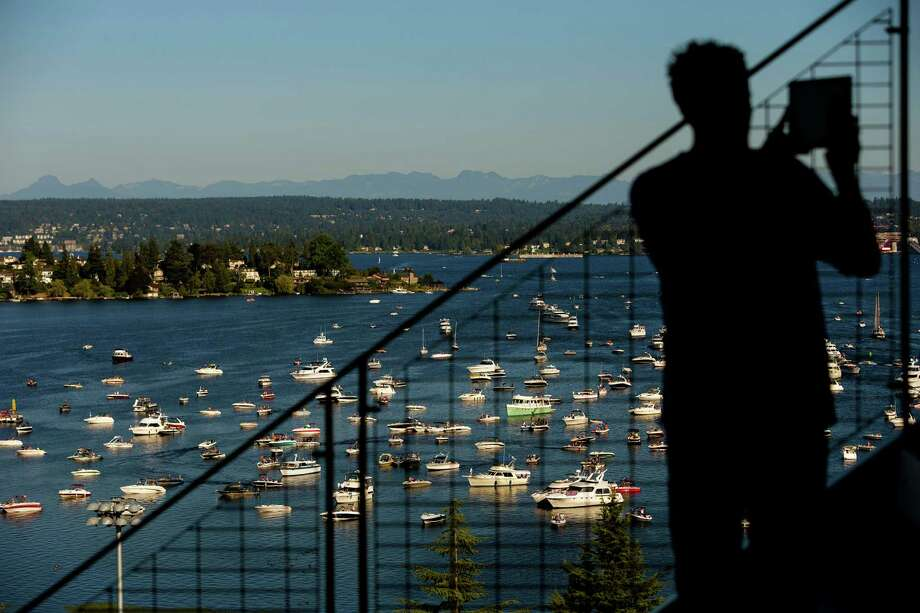 A man photographs a horizon of boats clustered on Lake Washington with a view of University of Washington's newly-renovated Husky Stadium before the opening season game against Boise State. Photo: JORDAN STEAD, SEATTLEPI.COM / SEATTLEPI.COM