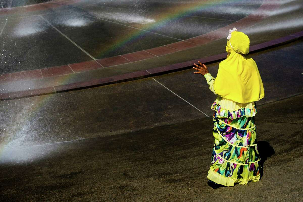 Symeyya Osman watches a rainbow form in the mist of the International Fountain following a Eid-ul-Fitr community prayer service at the Seattle Center in Seattle. The holiday celebrated by Muslims worldwide marks the end of Ramadan, the Islamic holy month of fasting.