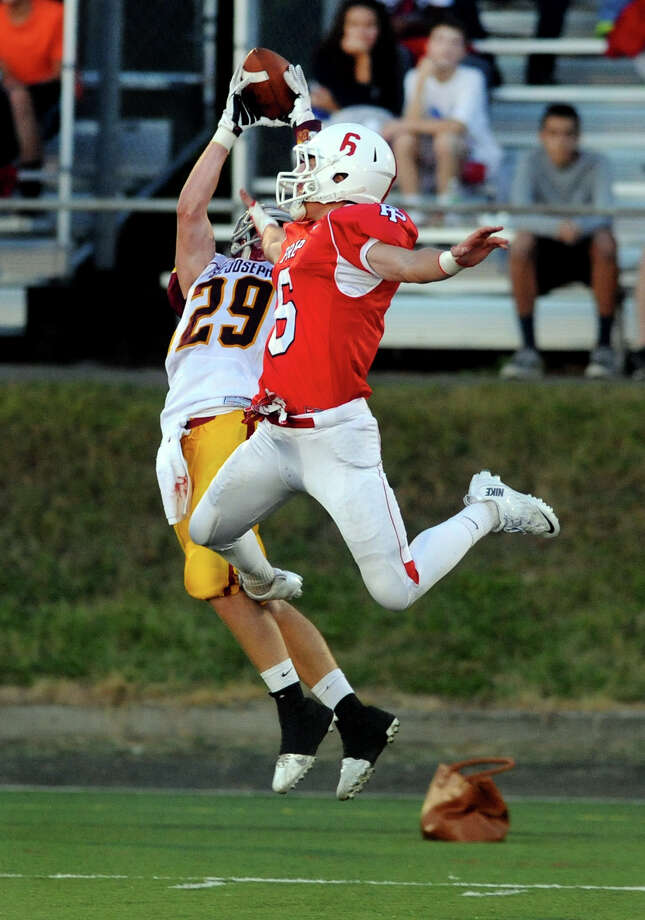St. Joseph's Lars Pedersen completes a pass, during high school football action against Fairfield Prep in Fairfield, Conn. on Friday September 20, 2013. Looking to disrupt the pass is Prep's Jake Buckley. Photo: Christian Abraham / Connecticut Post