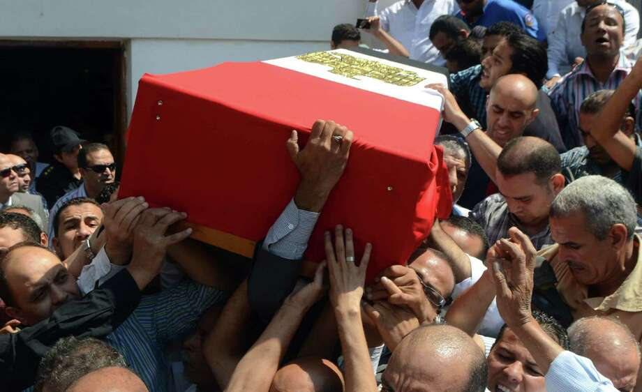 Egyptian mourners carry the casket of Giza security chief Nabil Farrag during his funeral outside Cairo.