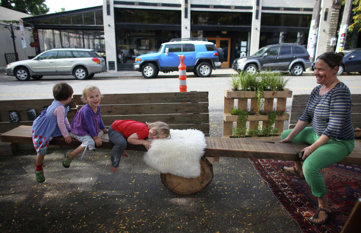 Carrie Barnes, right, rides on a teeter totter with kiddos at the Light Table Design Collective pop-up park on Ballard Avenue NW during PARK(ing) Day on Friday, Sept. 20, 2013. PARK(ing) Day is an event where businesses, community groups and individuals turn parking spaces into pop-up mini parks. There were about 40 of the parks across Seattle.