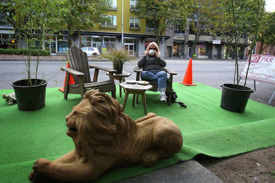 Kathy Biscardi sips her coffee at the Kaffeeklatsch and Dario's Statuary space during PARK(ing) Day at the space on Lake City Way. Photo: JOSHUA TRUJILLO, SEATTLEPI.COM / SEATTLEPI.COM